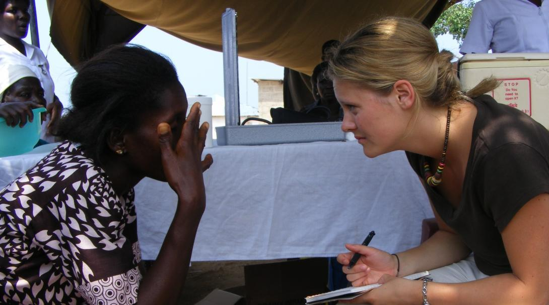 Female medical intern sits across a woman with a pad during Community Outreach programme in Ghana.